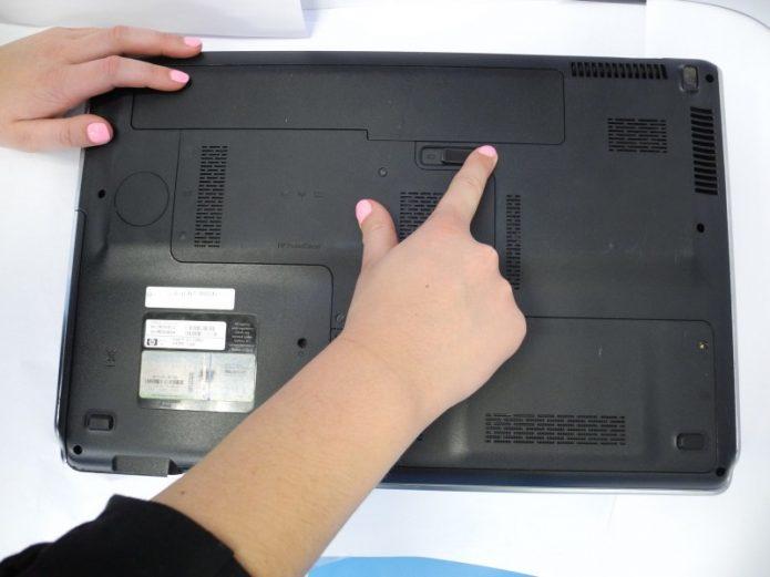 Защёлка, фиксирующая батарейный отсек, на задней крышке ноутбука