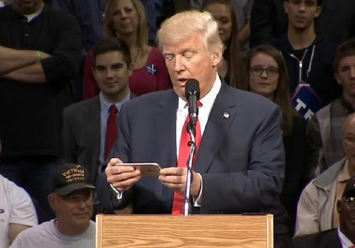 Трамп читает с экрана айфона