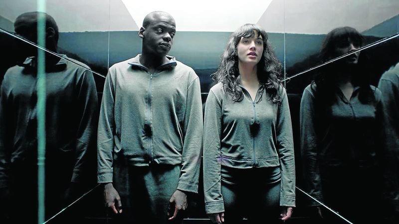 Афроамериканец и брюнетка в одинаковой одежде в лифте